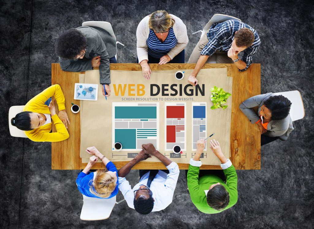 A group of web design experts sorrounding the rectangular table planning for a web design - Infintech Designs