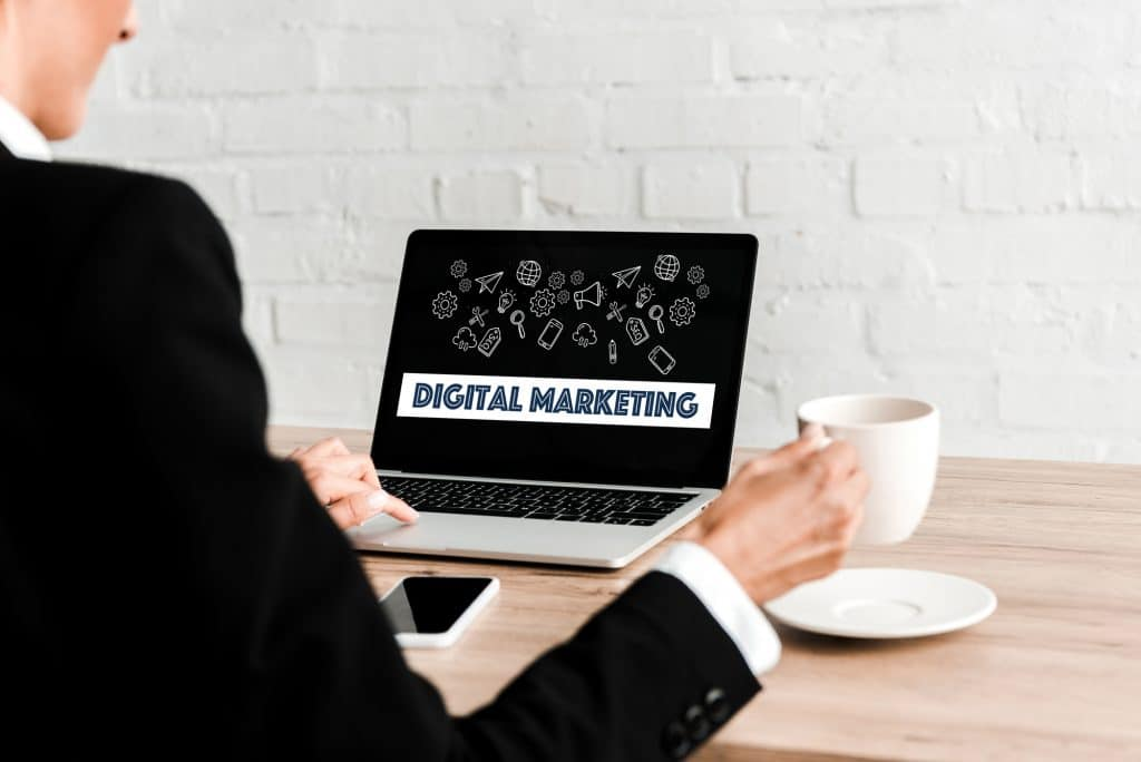 """woman holding a cup while sitting near a laptop with """"digital marketing"""" text on the screen and a smartphone with blank screen - Infintech Designs"""